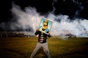 CREDIT: Moises Saman CAPTION: A Qaddafi supporter holds a portrait of the Libyan leader YEAR: March 9, 2011 MEDIUM, SIZE: COPYRIGHT: Courtesy of Magnum Photos